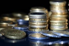 Many euro coins stacked on black. Background stock photography