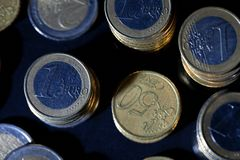 Many euro coins stacked on black. Background royalty free stock photography