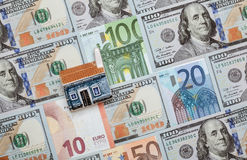 Many euro and dollar banknotes and toy house Stock Photos