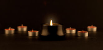 Many extinguished and one burned candle Stock Photo
