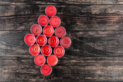 Many extinguished red candles in diamond shape on wooden table Royalty Free Stock Photography