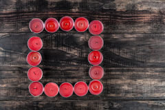 Many extinguished red candles in square shape on wooden table Royalty Free Stock Image