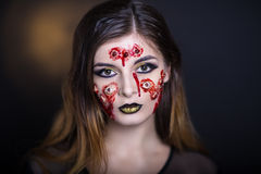 Many eyes horror. Horror make-up. Beautiful girl with creative grim for the Halloween party or film. Bright colors faceart, face design, golden black lips Royalty Free Stock Image