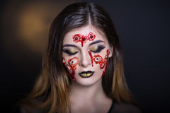 Many eyes horror. Horror make-up. Beautiful girl with creative grim for the Halloween party or film. Bright colors faceart, face design, golden black lips Royalty Free Stock Photo