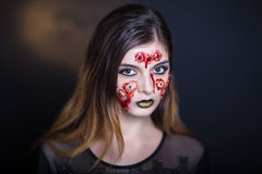 Many eyes horror. Horror make-up. Beautiful girl with creative grim for the Halloween party or film. Bright colors faceart, face design, golden black lips Royalty Free Stock Photos