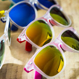 Many fashion colorful sunglasses on a wooden background Royalty Free Stock Photo