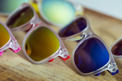 Many fashion colorful sunglasses on a wooden background Royalty Free Stock Image