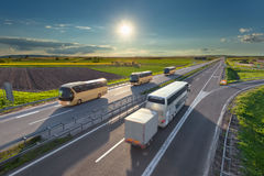 Many fast travel buses on the highway at sunset. Many modern buses driving in blurred motion on the freeway at beautiful idyllic sunny day. Transport and travel Royalty Free Stock Photo