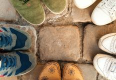Many feet in colorful sneakers stand in circle on stone,sport concept, copy space royalty free stock photo