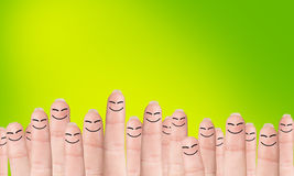 Many fingers with drawn faces. Stands on the green background Royalty Free Stock Photo