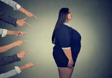 Many fingers pointing at fat woman. Many fingers pointing at fat young woman Royalty Free Stock Image