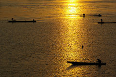 Many Fisherman paddling rowboat to fishing when sunset, Silhouet Royalty Free Stock Photos