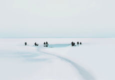 Many fishermen sit on the ice and fishing in winter cold Stock Image