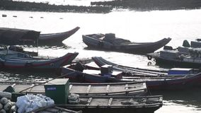 Many fishing boats are anchored by the sea. The sea is ebbing, and the sea under the setting sun stock video footage