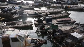 Many fishing boats are anchored by the sea. The sea is ebbing, and the sea under the setting sun stock footage