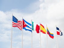 Many flags of different countries. Many colorful national flags of different countries on masts outdoor on blue cloudy sky background, symbols of usa cuba Royalty Free Stock Photos