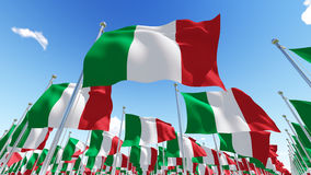 Many flags of Italy on flagpoles against blue sky. Royalty Free Stock Image