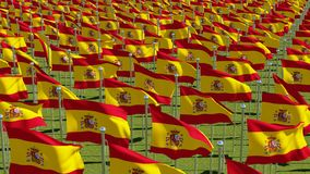 Many flags of Spain in green field. Royalty Free Stock Photography