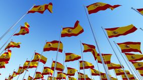 Many flags of Spain waving against blue sky. Royalty Free Stock Image