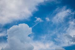 Many fluffy clouds on a blue sky. The trace of a plane that enters in the clouds royalty free stock photos