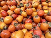 Many fresh fruits persimmons in supermarket, food concept background. Many fresh fruits persimmons in supermarket, food background stock image