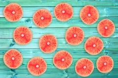 Many fresh grapefruit slices on blue wooden planks, summer concept. Many fresh grapefruit slices on blue wooden planks, summer background concept Royalty Free Stock Image