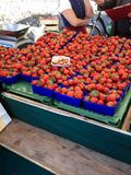 Many fresh strawberries arranged in basket for sale at outdoor market stall in street marketplace. Agriculture, Food, Farm concept Stock Photography