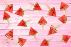Many fresh watermelon popsicles on pink wooden planks, summer background royalty free stock photos