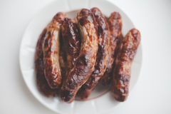 Many fried grill sausages on plate on white background Stock Photos