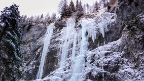 Many frozen waterfalls with extreme ice climbers on them on a cold winter day in the Dolomites in Italy. Near Sottoguda Stock Image