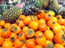 Many fruits persimmon and pineapples lying in supermarket Royalty Free Stock Photography