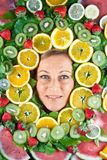 Fruits and blond cute woman portrait. Many fruits stacked together around the head of a cute blond woman stock photo