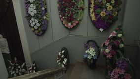 Many Funeral Wreaths. With red and white flowers on a wall stock video footage