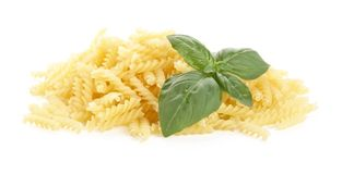 Many fusilli pasta with basil leaves isolated on white Royalty Free Stock Photo