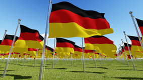 Many German flags blowing in the wind in green field. Royalty Free Stock Photo