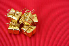 Many Gifts. Small golden christmas gifts on a red background Royalty Free Stock Photos