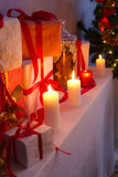 Many gifts near a Christmas tree in the candlelight Stock Image