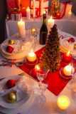 Many gifts near a Christmas tree in the candlelight Stock Photo