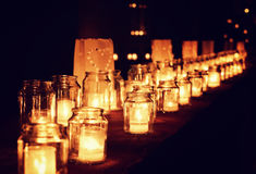 Many glass jars with burning candles royalty free stock image