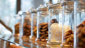 Many glass jars with caps filled with cookies and sweets, on defocused background with reflection. Jars contain marsh-mallow and royalty free stock image