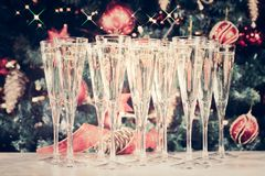 Glasses of champagne with Christmas tree background and sparkles. Many glasses of champagne with Christmas tree background. Party setup. Holiday season Royalty Free Stock Photo