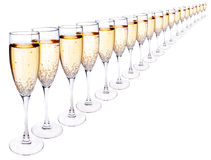 Many glasses of champagne in a row. Many champagne glasses full of bubbly,in a line,isolated on white Stock Photo