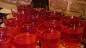 Many glasses with red cherry juice. On the table stock footage