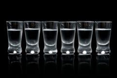 Many glasses of vodka isolated on black background Stock Image