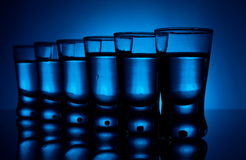 Many glasses of vodka lit with blue backlight Royalty Free Stock Image
