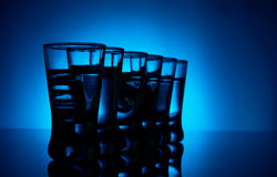 Many glasses of vodka lit with blue backlight Royalty Free Stock Photography