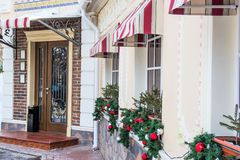 Many glittering, shiny Christmas tree balls, decoration on windows of a restaurant, cafe. Brick wall, door stock photography