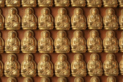 Many Gold Buddha sculptures on the wall Stock Photos