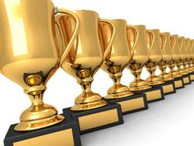 Many gold trophies in a row. High quality render of many gold trophies in a row, isolated over white Royalty Free Stock Images