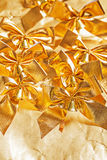 Many golden bows on paper background Stock Photography